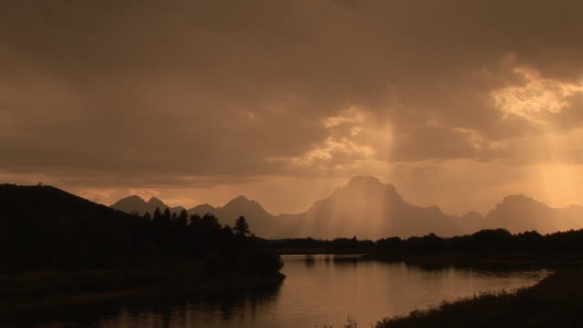 WS, PAN, Silhouette of mountain range and river with sun shining through clouds, Grand Teton National Park, Wyoming, USA