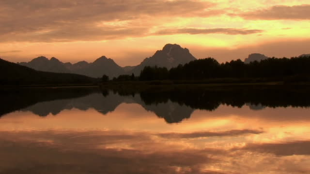 stockvideo's en b-roll-footage met  ws, silhouette of mountain range and snake river at sunset, grand teton national park, wyoming, usa - sepiakleurig
