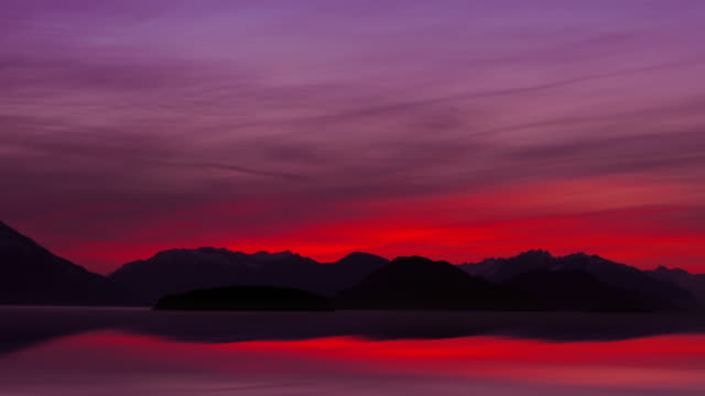 Silhouette of mountain range with purple and red sky in Alaska.