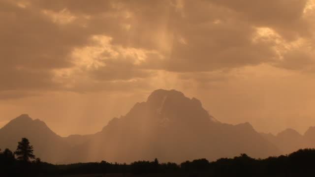 vídeos y material grabado en eventos de stock de ws, pan, silhouette of mountain range with sun shining through clouds, grand teton national park, wyoming, usa - cordillera tetón