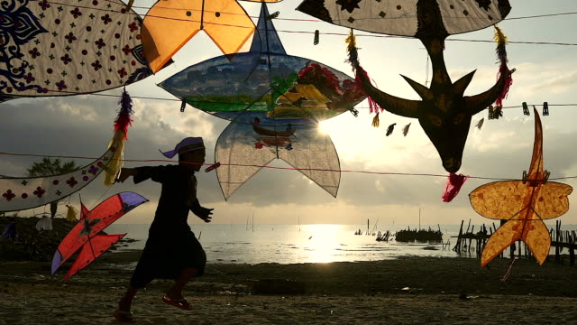 Silhouette of Muslim child flying a kite with the traditional kite as foreground.