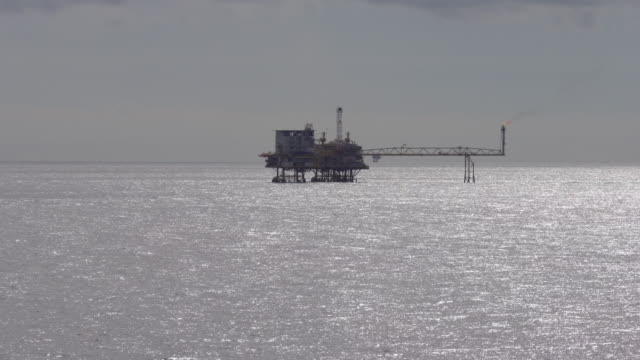 silhouette of oil platform in the ocean - oil drill stock videos and b-roll footage