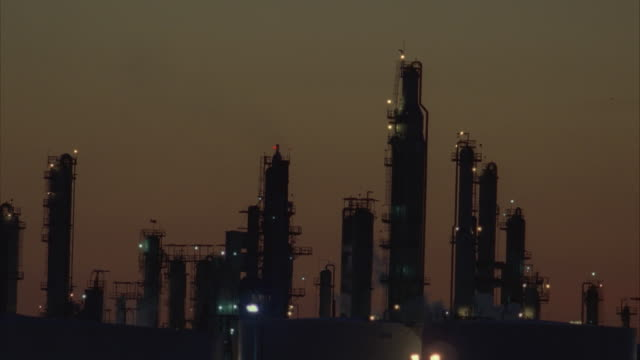 vídeos y material grabado en eventos de stock de ws, silhouette of oil refinery at dusk - 1996