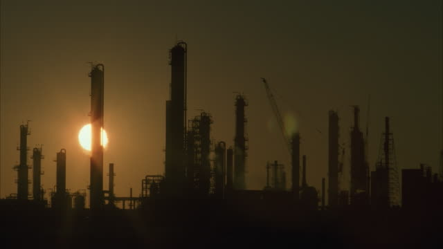 vídeos y material grabado en eventos de stock de ws, silhouette of oil refinery at sunset - 1996