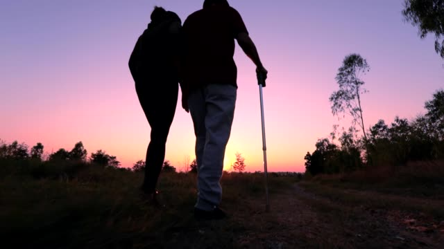 vídeos de stock e filmes b-roll de silhouette of old man using staff walking with his daughter during sunset, concept a rehabilitation after injury, slow motion - bengala acessório
