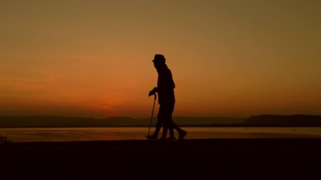 vídeos y material grabado en eventos de stock de silueta de hombre usando personal caminar con su hija durante la puesta del sol, concepto una rehabilitación después de lesiones, cámara lenta - enfermedad de alzheimer