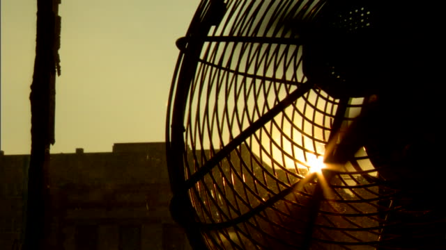 silhouette of partial fan by window, blades spinning, silhouette of unidentifiable buildings bg, bright sun & glare through spinning fan blades in... - ventilator stock-videos und b-roll-filmmaterial