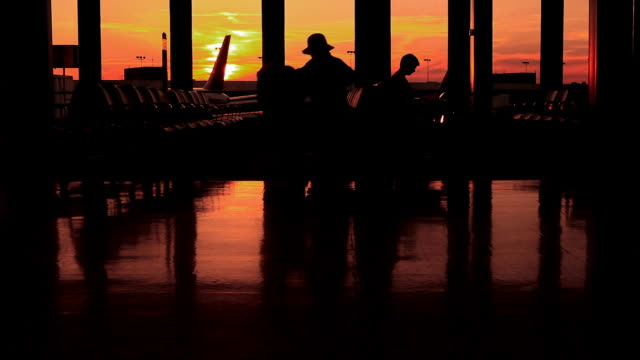 Silhouette of Passenger Reading and Using Idevices at Sunset in the Airport Terminal