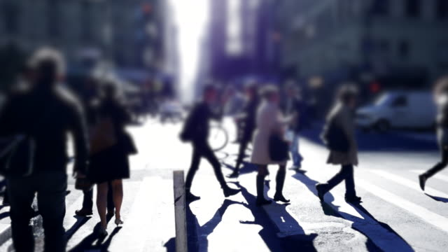 silhouette of pedestrians crossing street in the city. walking people background