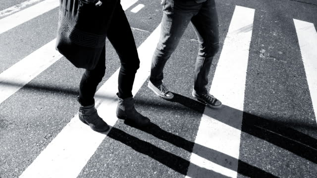 silhouette of pedestrians crossing street in the city. walking people background - dress shoe stock videos and b-roll footage