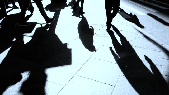 vídeos de stock, filmes e b-roll de silhouette of pedestrians crossing street in the city. walking people background - mala de rodinhas