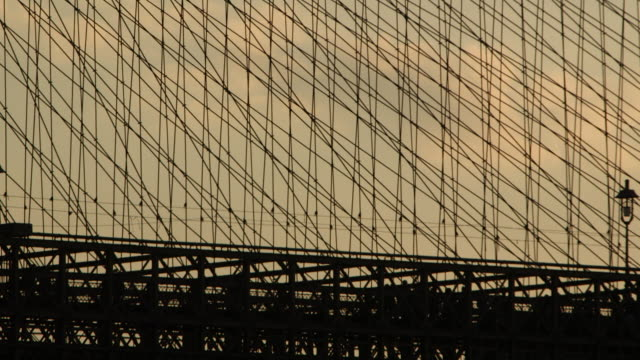 Silhouette of pedestrians walking on the Brooklyn Bridge at dusk.