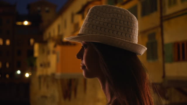 silhouette of pensive woman by ponte vecchio bridge looking out at river arno - ponte点の映像素材/bロール
