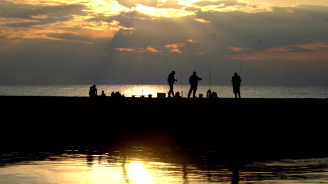 silhouette of people fishing on pier - fishing rod stock videos & royalty-free footage