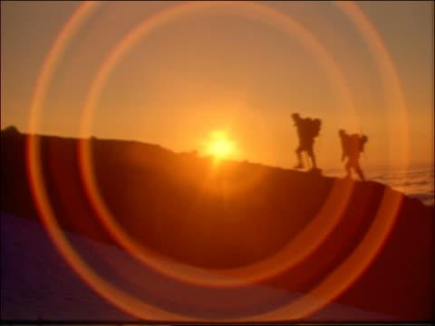 silhouette of people hiking on mountain at sunset - エコツーリズム点の映像素材/bロール