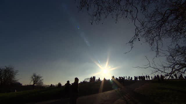 silhouette of people of hampstead heath, with sun shining, as people enjoy warm winter weather during coronavirus lockdown - competition stock videos & royalty-free footage