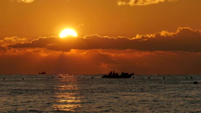 vídeos de stock e filmes b-roll de silhouette of people on a boat at sea and sunrise - 1 minuto ou mais