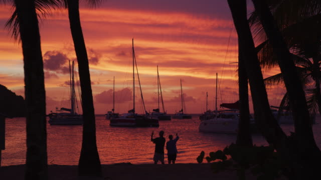 silhouette of people photographing boats at ocean beach during sunset / salt whistle bay, mayreau, saint vincent and the grenadines - toned image stock videos & royalty-free footage