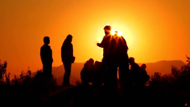 4 K Silhouette de personnes détente ensemble sur la falaise de la montagne pendant le coucher du soleil.