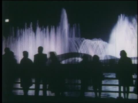 vidéos et rushes de pan silhouette of people standing walking near lit fountains at night / ny world's fair - exposition universelle de new york