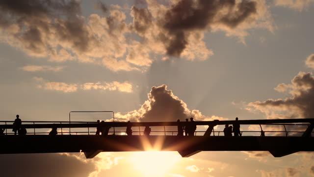 日落時分在倫敦千年人行天橋上行走的人的剪影 - 橫越 個影片檔及 b 捲影像