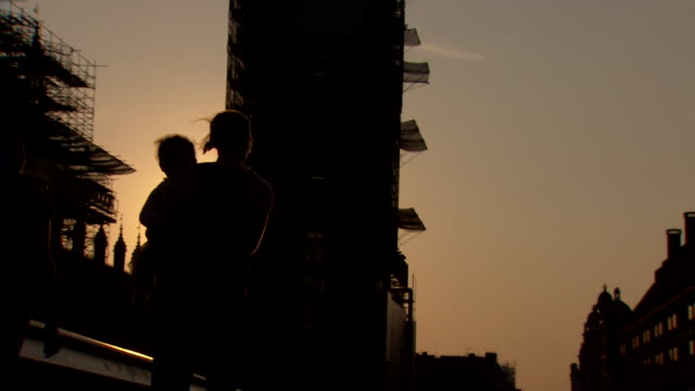 silhouette of people walking past houses of parliament at dusk - women politics stock videos & royalty-free footage