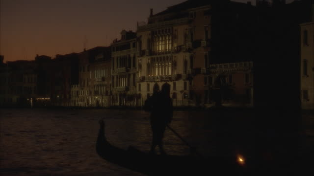 ms silhouette of person rowing gondola in grand canal at night / venice, italy - old town stock videos & royalty-free footage