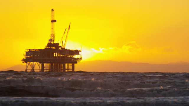 Silhouette of petroleum oil rig platform sunset USA