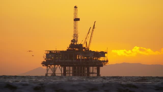 Silhouette of petroleum oil rig platform sunset USA