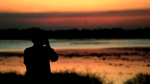 Silhouette of photographer against sunset, slow motion