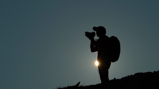 silhouette of photographer with backpack at sunset or sunrise - dorso umano video stock e b–roll
