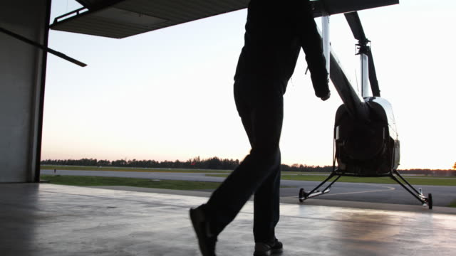 silhouette of pilot pushing helicopter out of hanger - airplane hangar stock videos and b-roll footage