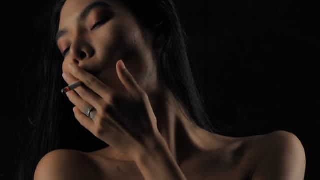 silhouette von portrait frau rauchen eine zigarette. abgeschnittene ansicht der nackten frau mit roten lippen, die rauch bläst, isoliert auf schwarz. lebensstil,krebs,gesundheitsversorgung und medizin,erotische bewegung,narcotic,versicherungskonzept. echt - fkk stock-videos und b-roll-filmmaterial
