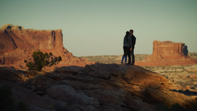 silhouette of romantic couple hugging and kissing in mountain landscape / moab, utah, united states - moab utah stock videos & royalty-free footage