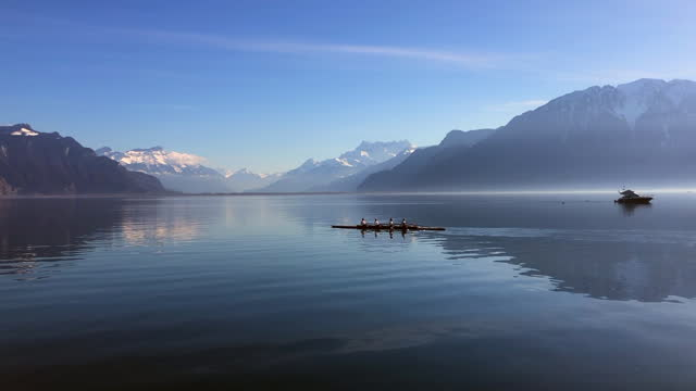 vidéos et rushes de silhouette of rowing team training on lake geneva near the city of montreux on a calm morning - montreux