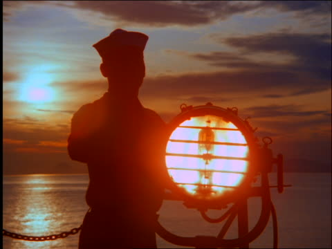 silhouette of sailor flashing signal light on ship on ocean at sunset / brazil - sailor suit stock videos and b-roll footage