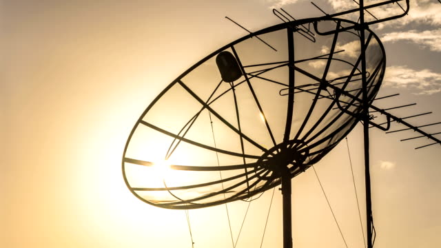 silhouette of satellite dish at sunset - disk stock videos and b-roll footage
