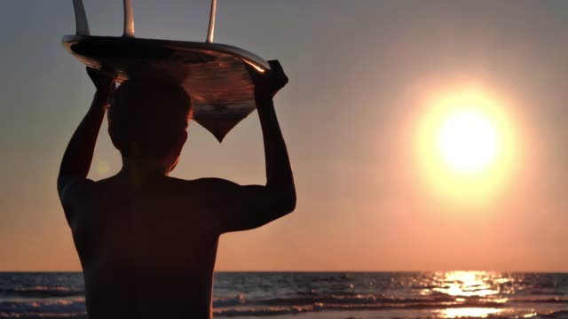 silhouette of senior man carrying surfboard on head at beach during sunset.real bodies - surfboard stock videos & royalty-free footage