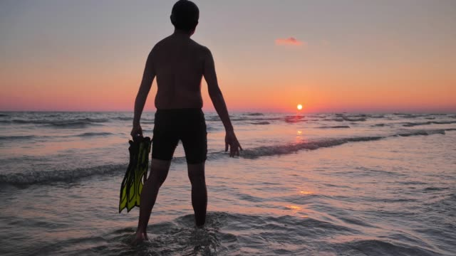silhouette of senior man holding mask and flippers for swimming on the sea in sunset.senior man relaxing on summer holidays.real bodies - diving flipper stock videos & royalty-free footage