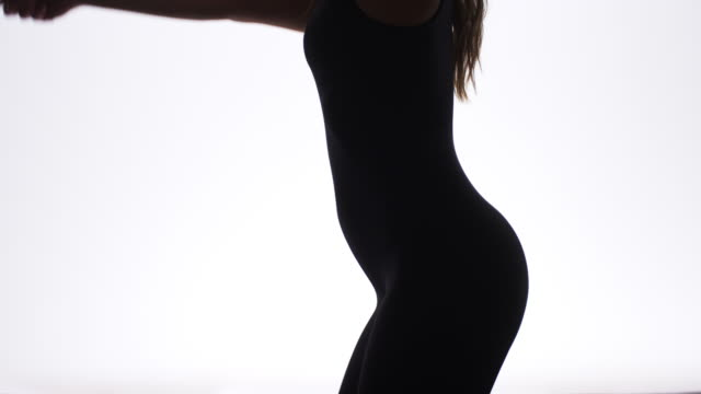 Silhouette of sexy woman dancing in slow motion