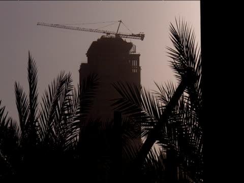 silhouette of skyscraper under construction palm trees in foreground dubai - erezione video stock e b–roll