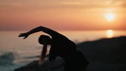 Silhouette of sportswoman practicing morning warming up on beach. Shot on RED Raven 4k Cinema Camera
