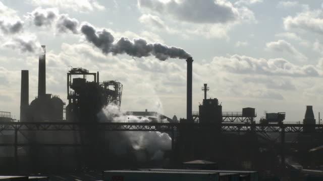 vídeos de stock e filmes b-roll de ws silhouette of steel mill with smokestack emitting smoke against sky / duisburg, north rhine westphalia, germany - mill