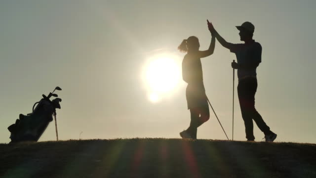 vídeos de stock e filmes b-roll de silhouette of success golfers team on green golf field.celebration,success,teamwork,collaboration,support,togetherness.confidence,leadership,power,skill,strength, friendship,concept.sports cinemagraphs.personal trainer - golfe
