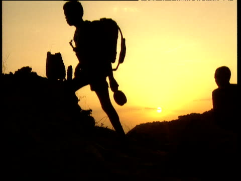 Silhouette of Sudan Peoples' Liberation Army soldiers climbing over rocky landscape against setting sun