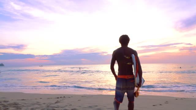 vídeos de stock, filmes e b-roll de silhueta de homem surfista na praia - surf
