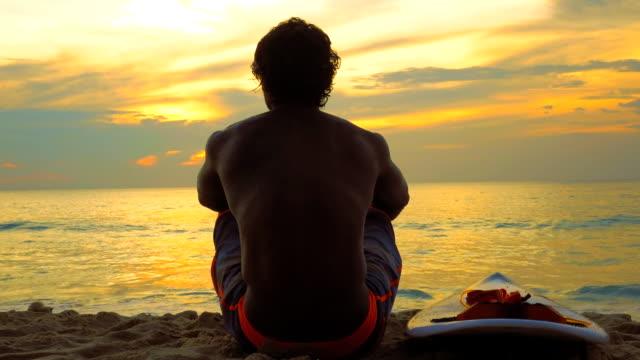 vídeos de stock, filmes e b-roll de silhueta de homem surfista sentado na praia mar - sentando