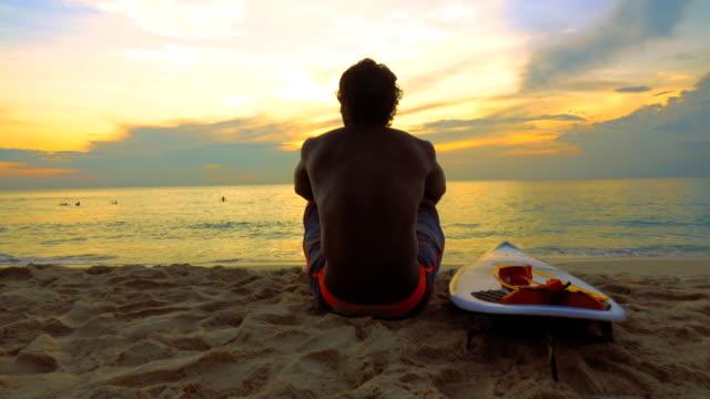 vídeos y material grabado en eventos de stock de silueta de hombre surfer sentado en la playa del mar - surf en longobard