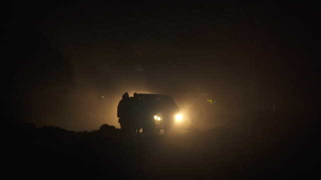 Silhouette of Syrian Democratic Forces moving through street at night in Deir ezZor Syria