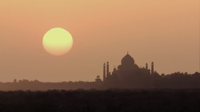ws silhouette of taj mahal against orange sky at sunrise / agra, uttar pradesh, india - taj mahal stock videos and b-roll footage